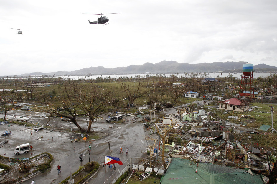 Image: Helicopters hover over the damaged area after super Typhoon Haiyan battered Tacloban city